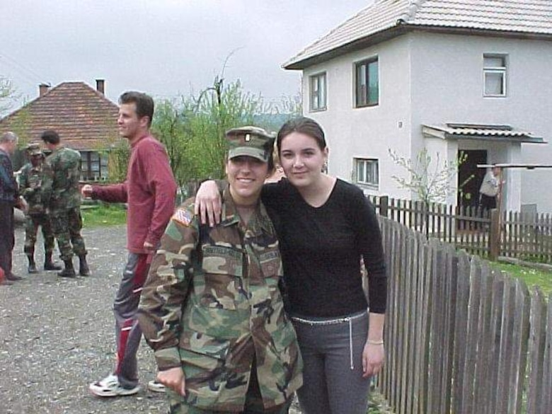Now-Air Force Lt. Col. Elizabeth Hoettels, 423rd Medical Squadron commander, poses for a photo during a deployment in Bosnia with one of the locals, Samra, during her prior career as an Army Civil Affairs officer. Hoettels served 10 years in the Army before transitioning to the Air Force. (Courtesy photo)