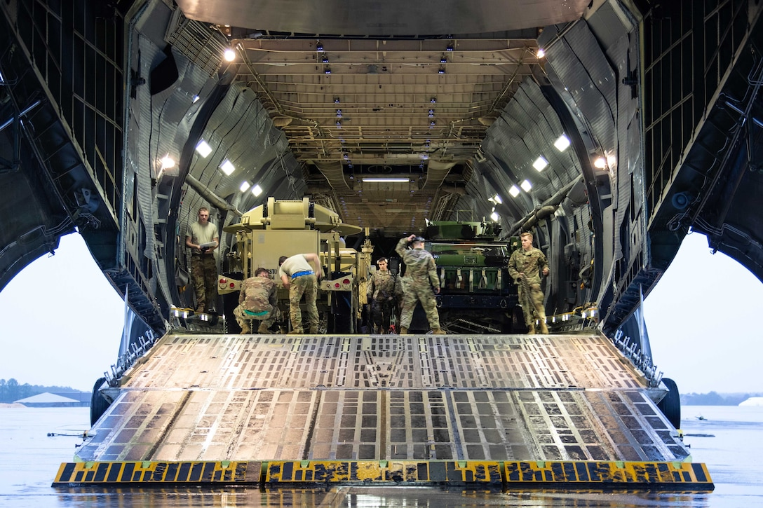 Soldiers load equipment into a large military aircraft.