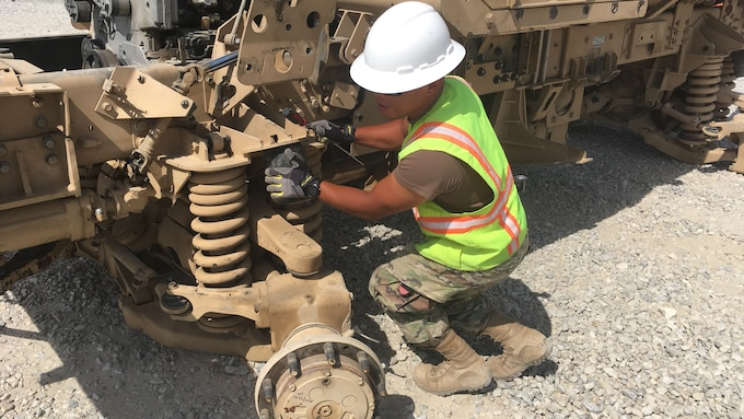 Navy Petty Officer Second Class Jhunar Medenilla performs an ammo abatement inspection on a vehicle