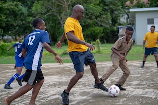 Sailors assigned to the Freedom-variant littoral combat ship USS Detroit (LCS 7) play soccer with students during a community relations event at Ocho Rios Primary School.