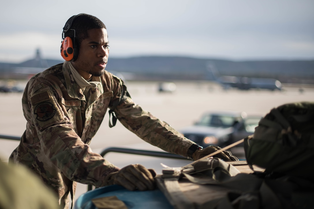 U.S. Air Force Senior Airman Kenneth Saunders, 435th Contingency Response Squadron mobile aerial porter, pushes a pallet onto a C-130J Super Hercules aircraft during Exercise Agile Wolf at Ramstein Air Base, Germany, Dec. 17, 2019. The 435th provides U.S. Air Forces in Europe's primary expeditionary aerial port capability and performs initial airfield operations enabling rapid standup of combat operations anywhere in the European region. (U.S. Air Force photo by Staff Sgt. Devin Nothstine)