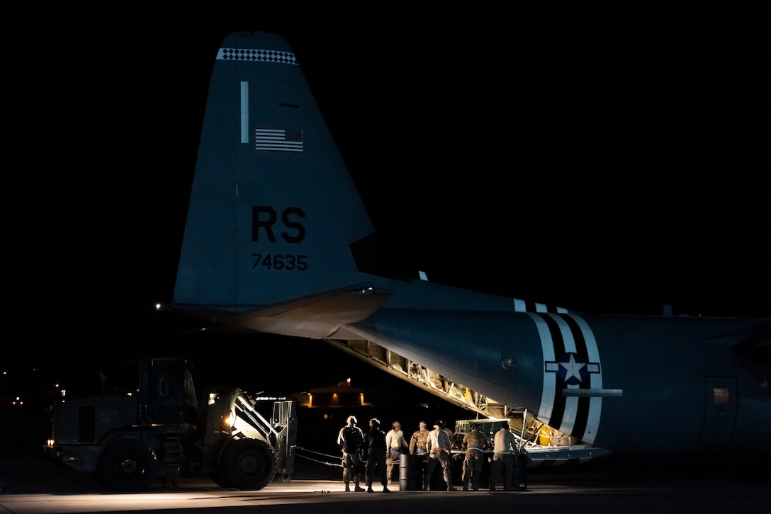 U.S. Airmen assigned to the 435th Contingency Response Squadron conduct combat offload method-B training at night during Exercise Agile Wolf at Ramstein Air Base, Germany, Dec. 17, 2019. Combat offload method-B allows the 37th Airlift Squadron to deploy cargo in austere locations without access to large mobility vehicles. (U.S. Air Force photo by Staff Sgt. Devin Nothstine)