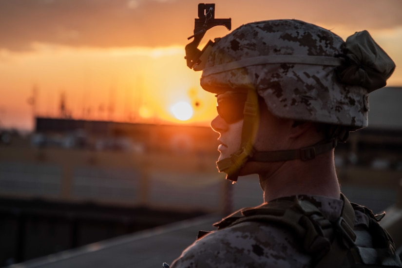 A Marine stands watch at his post with the sun behind him.