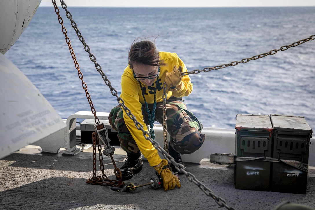 A kneeling sailor manipulates chains on a flight deck.
