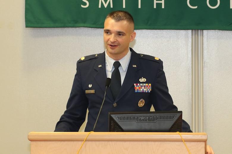 An Airman stands a podium and gives a speech