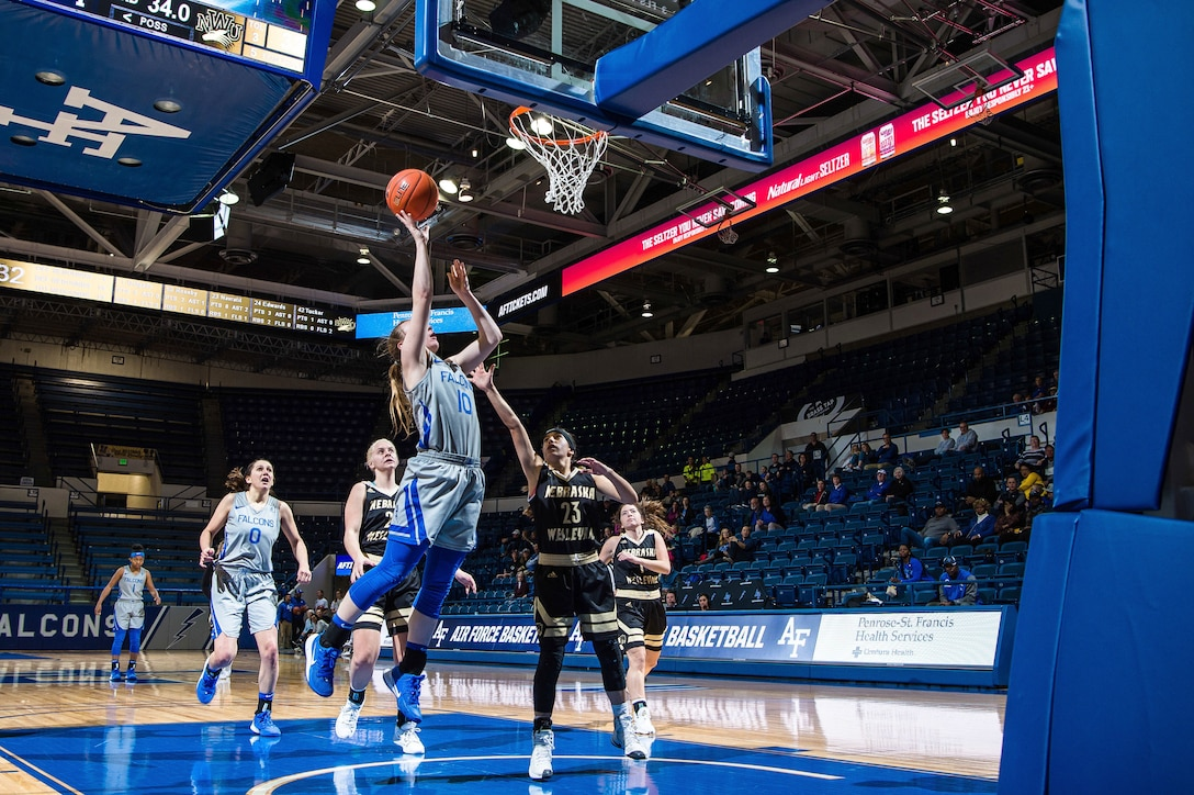 An Air Force basketball player jumps with the ball.