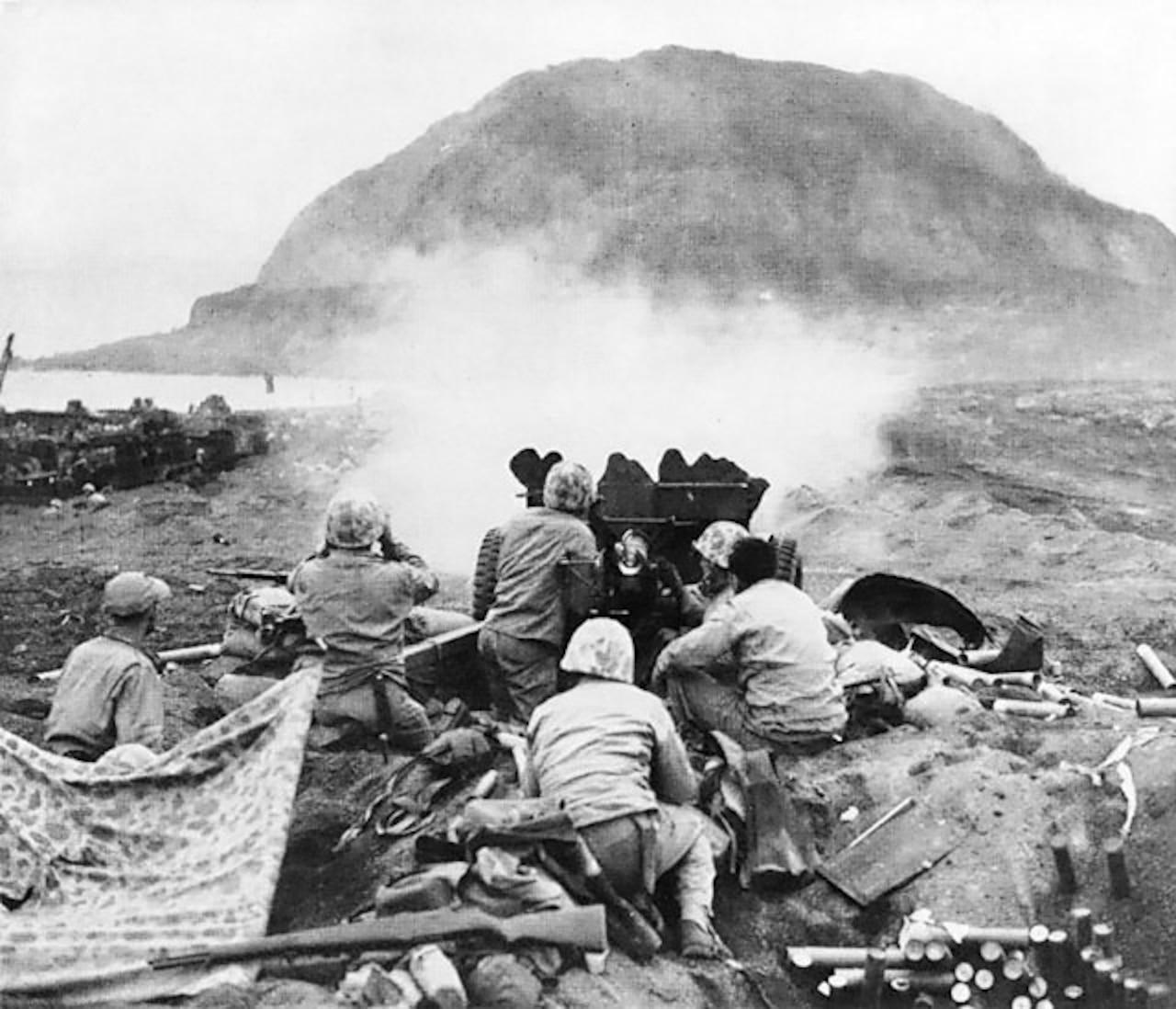 Marines fire artillery.