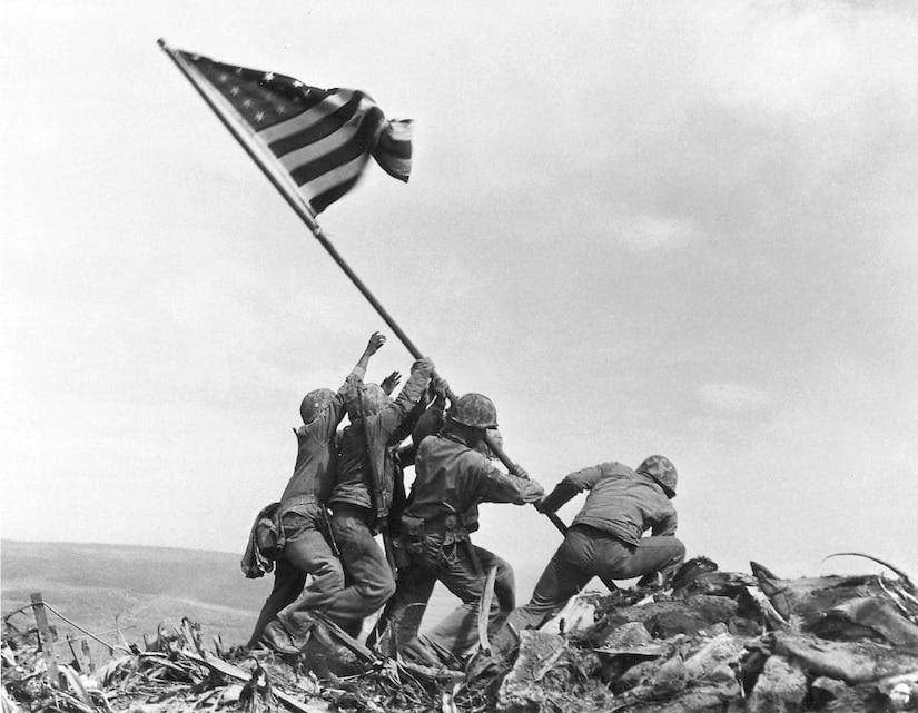 U.S. service members in combat gear raise a flag.