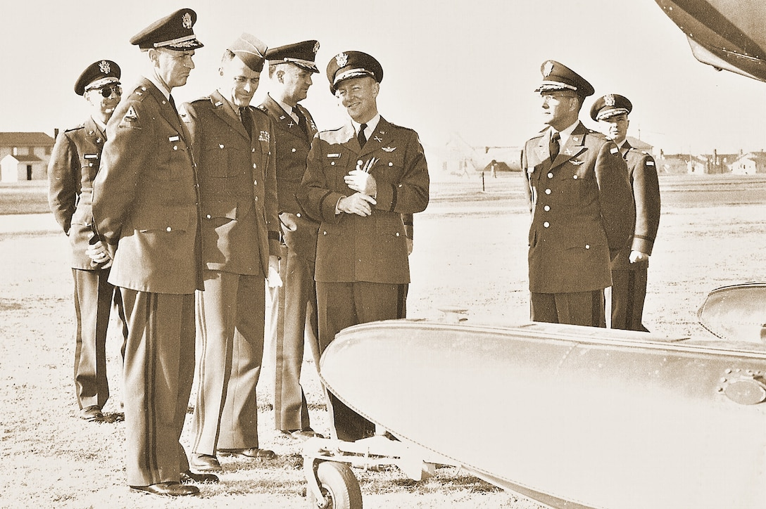 Several high-level military officials in dress uniforms and caps chat beside the wing of an airplane on an airfield.