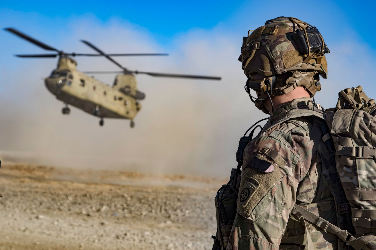 A soldier watches as a helicopter approaches the ground, kicking up dirt.