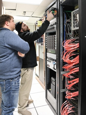 Dakota Aaron, right, an eSTARR hardware engineer, and Calvin Davis, an instrumentation, data and controls engineer, check the new network switch and data source computers in the Arnold Engineering Development Complex Engine Test Facility T-3 test cell data conditioning room at Arnold Air Force Base, Tenn., Dec. 3. The network switch and data source computers are part of upgrades to the test cell, including the new digital voltage scanners at the right. (U.S. Air Force photo by Jill Pickett)