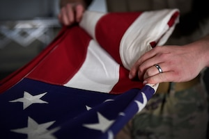 A man folds a flag.