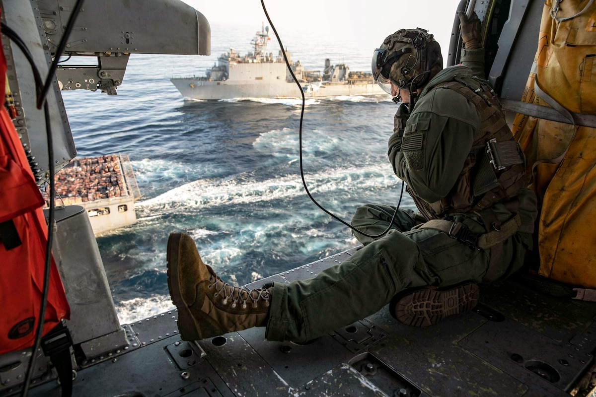 A sailor aboard an open aircraft looks out over two ships in the ocean.