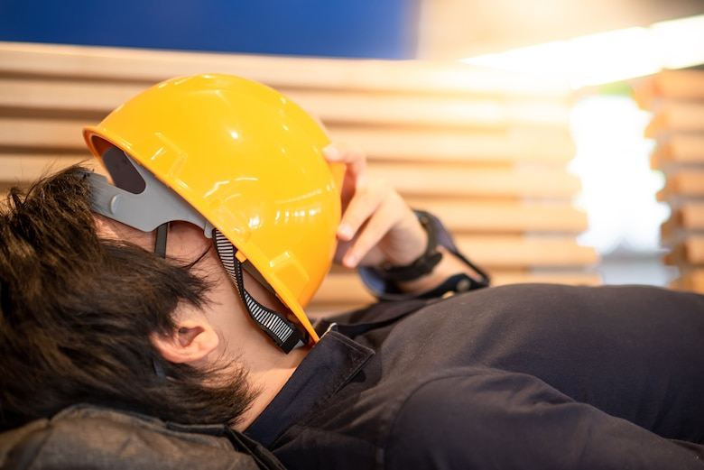 Photo shows laborer sleeping with hardhat laying across face.
