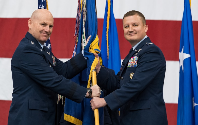 Maj. Gen. Sam C. Barrett, left, 18th Air Force commander, presents the 436th Airlift Wing guidon to Col. Matthew Jones, incoming 436th AW commander, during a change of command ceremony Jan. 7, 2020, inside the 436th Aerial Port Squadron, on Dover Air Force Base, Del. Upon taking command, Jones became the wing's 35th commander. (U.S. Air Force photo by Roland Balik)