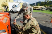 U.S. Air Force Staff Sgt. Edwin Marrero, left, a cyber infrastructure technician and Senior Airman Edwardo Mendez, an information technology specialist with the 156th Communications Flight at Muñiz Air National Guard Base, Puerto Rico Air National Guard, perform maintenance on a generator f in Cayey, Dec. 27, 2019. Airmen from the 156th Wing were activated to support state and federal operations working to stabilize a vegetation debris fire that has been burning underground in Cayey since Nov. 28, 2019.