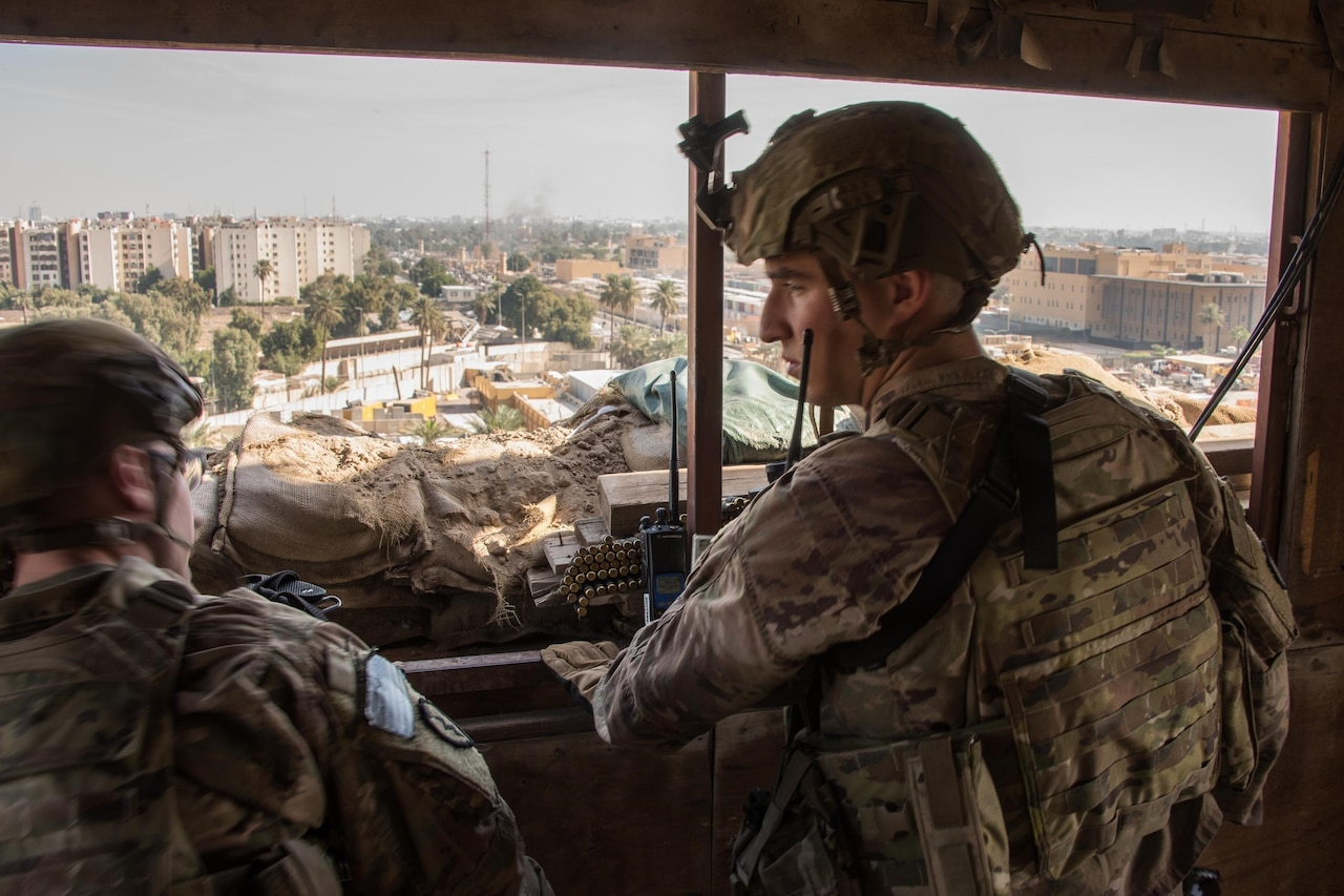 Two soldiers stand in a window of a guard tower.
