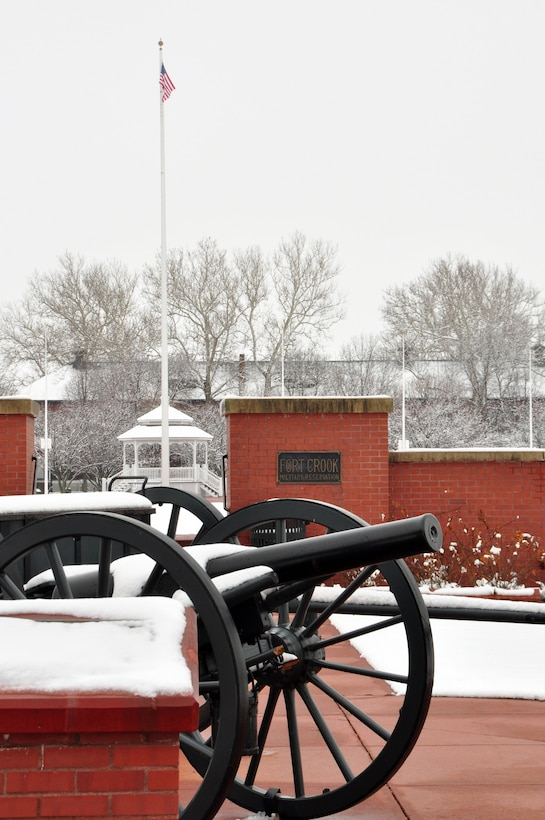 Offutt parade grounds, covered in snow, with cannon in foreground and gazebo in distant background