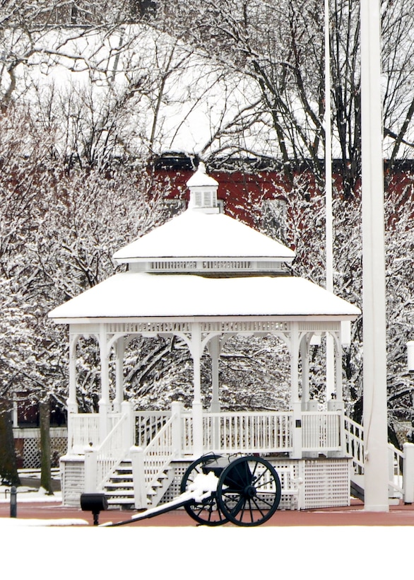 snow resting on gazebo on parade grounds, with cannon in the foreground