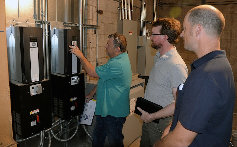 Shane Jepson, facility manager for building 220, shows ISO 50001 auditors Jonathan Clark and Rob Ellis, newly installed variable frequency drive monitors located on the wall of a utility room.