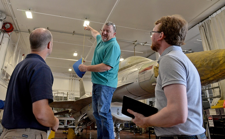 Shane Jepson, facility manager for building 220, points at new energy saving light fixtures on the ceiling in a depot maintenance facility to auditors Rob Ellis (left) and Jonathan Clark