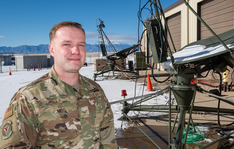 An Air Force Reserve enlisted member stands near satellite communications equipment