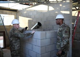 An Airman talks to another Airman in a building that is under construction.