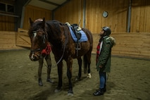 A U.S. Marine with Marine Rotational Force-Europe 20.1, Marine Forces Europe and Africa, prepares to mount a horse while visiting a Norwegian family for Host-A-Marine, in Setermoen, Norway, Dec. 27, 2019.