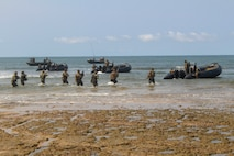 U.S. Marines with Special Purpose Marine Air-Ground Task Force-Crisis Response-Africa 20.1, Marine Forces Europe and Africa, and Belgian Army soldiers with the Special Operations Regiment withdraw from the beach during an amphibious landing demonstration during the closing ceremonies for Exercise Tropical Storm in Akanda, Gabon, Dec. 15, 2019.
