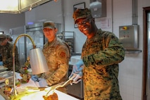 A U.S. Air Force airman with 496th Tactical Fighter Squadron, and a U.S. Marine with Special Purpose Marine Air-Ground Task Force-Crisis Response-Africa 20.1, Marine Forces Europe and Africa, serves Christmas food to fellow Marines and Sailors at Morón Air Base, Spain, Dec. 25, 2019.
