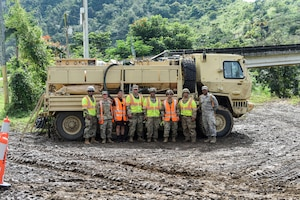 U.S. Air Force Airmen, assigned to the 156th Wing, Puerto Rico Air National Guard, and U.S. Army Soldiers, assigned to the 482nd Chemical Company, Puerto Rico National Guard, pose in front of a vehicle near Rio de la Plata, Puerto Rico, Dec. 27, 2019. Members of the Puerto Rico National Guard were activated to support state and federal operations working to stabilize the vegetation debris fire that has been burning underground in Cayey, Puerto Rico, since Nov. 28, 2019. (U.S. Air National Guard photo by Master Sgt. Caycee Watson)