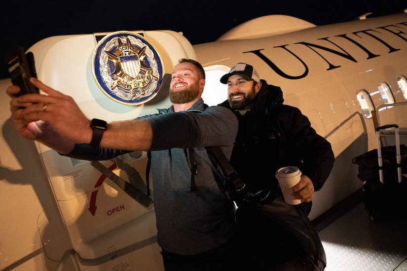 Two bearded men take a selfie at the door or a military aircraft that bears the seal of the Joint Chiefs of Staff on its door.