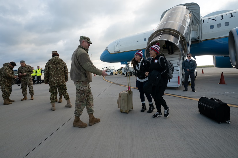 Service members in uniform greet USO Tour participants as they file off their airplane.
