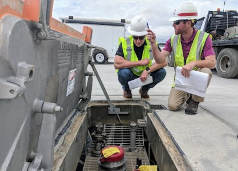Matt Peterson (left), POL-MCX mechanical engineer, inspects a hydrant pit prior to tuning while Matthew Hoyle, Civil Engineer/Office Engineer, Savannah District, locates adjacent hydrant fuel pits along the Green Ramp at Pope Army Airfield, North Carolina.  (Photo by Greg Etter)