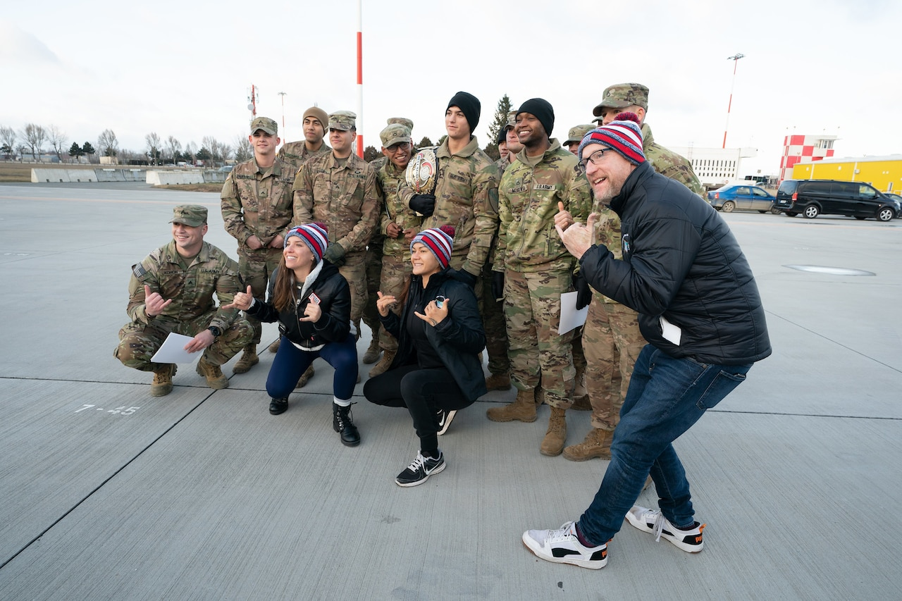 Service members pose with USO Tour participants on a flightline.