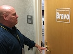 Man stands in front of office door with sign indicating the force protection condition is Bravo.