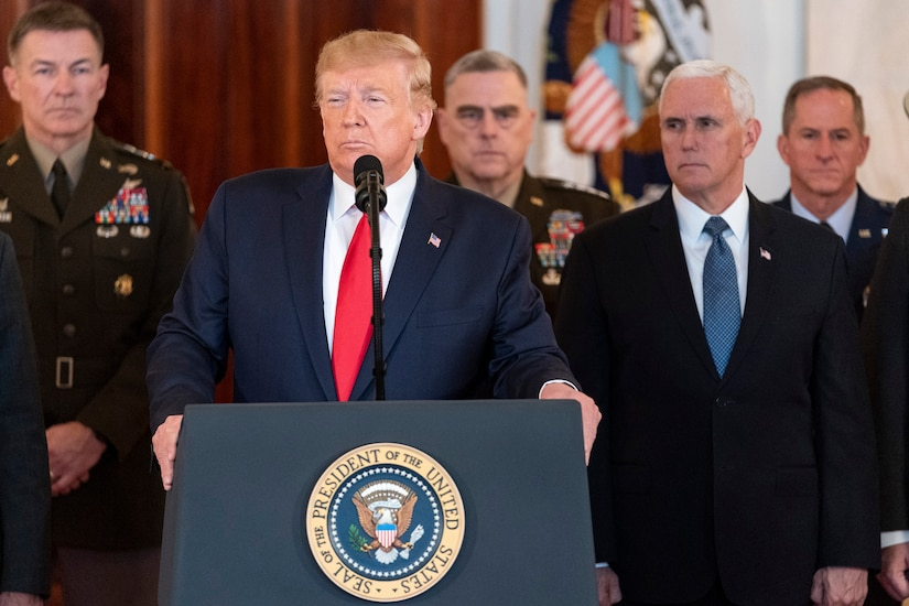 President Donald J. Trump stands at a podium speaking to the press, with senior advisors standing behind him.