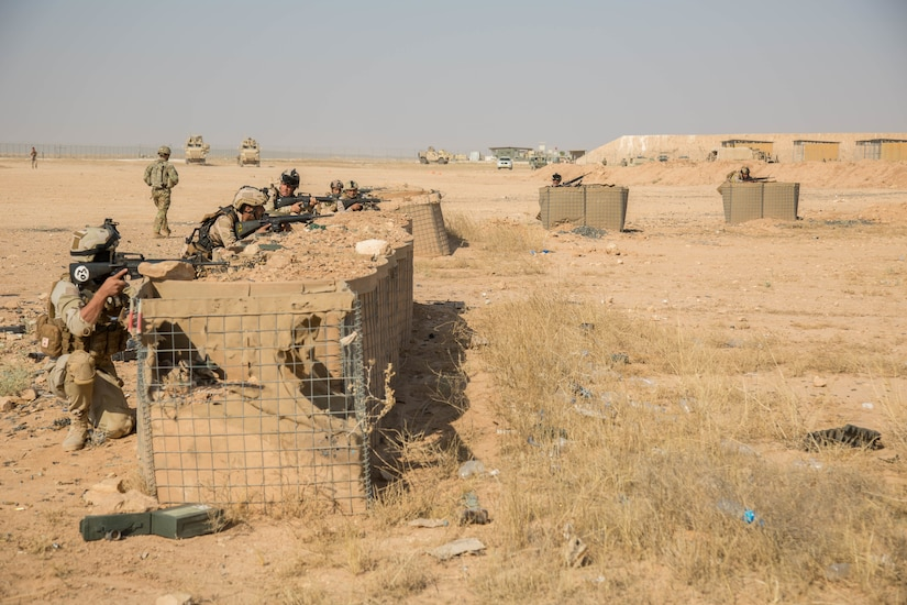 Soldiers in a desert setting fire weapons from behind barricades.