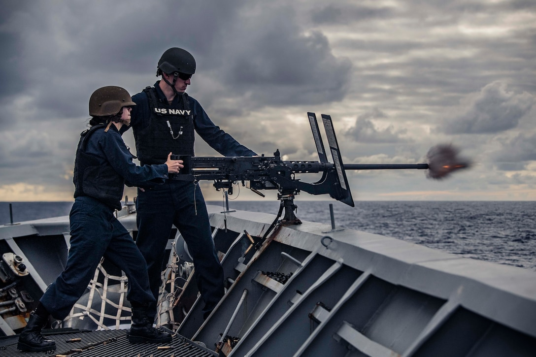 Two sailors stand next to each other as one fires a machine gun.