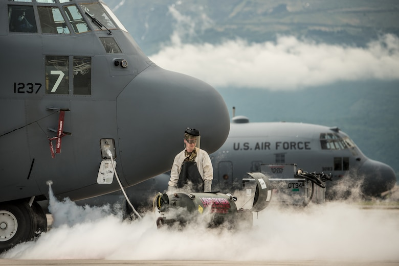 Senior Airman services the liquid oxygen system of a C-130 Hercules