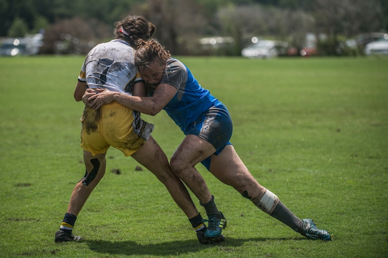 An Air Force rugby player tackles a Navy rugby player during a tournament