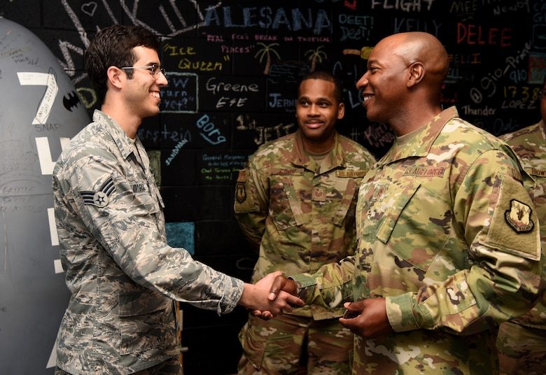CMSAF presents a coin to Senior Airman