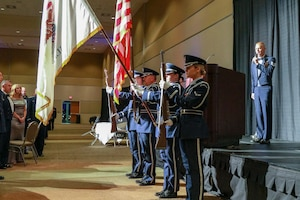 Vocalist singing as color guard presents colors.