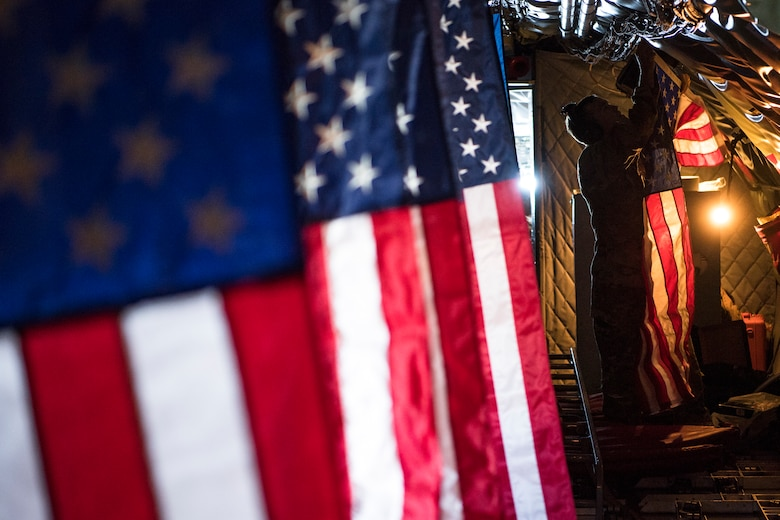 Pilot hangs the American flag inside a KC-135 Stratotanker