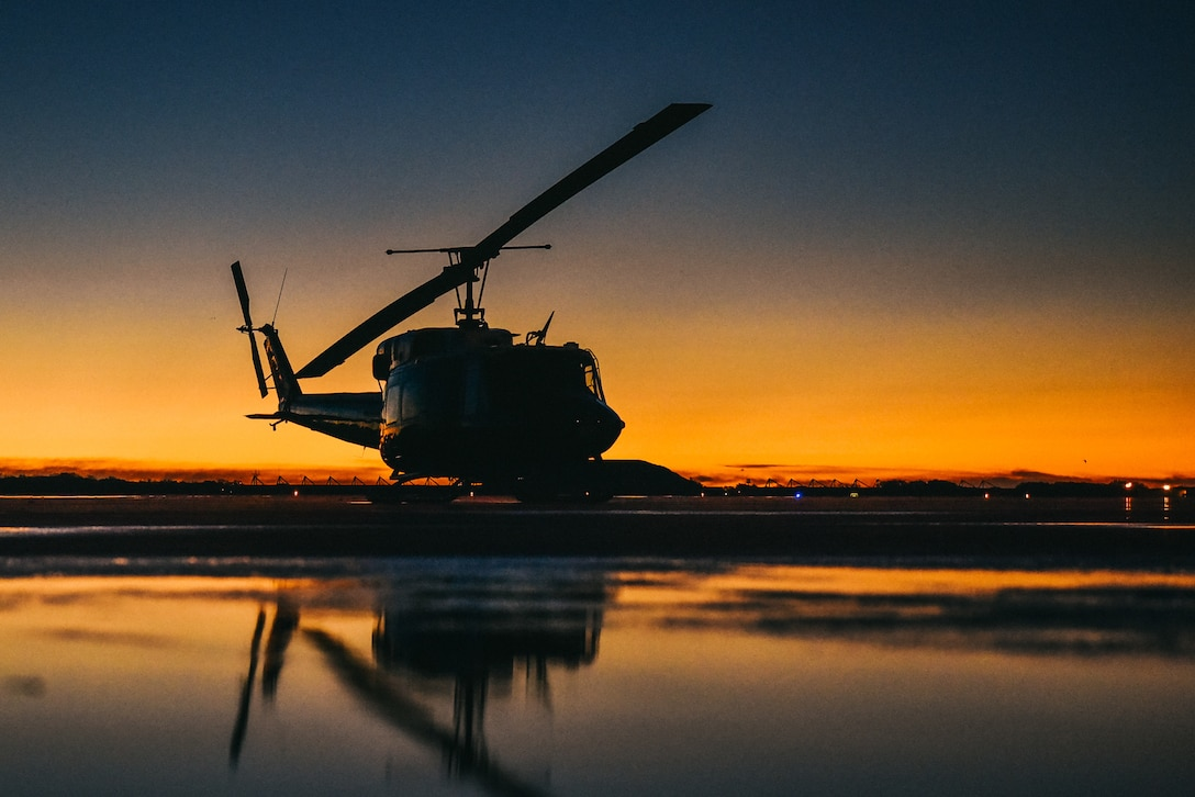 A UH-1N Iroquois sits on the flightline
