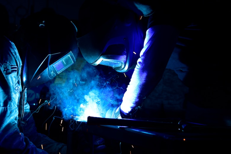 Airman apprentice, left, assists welder, as he welds a metal bar in place