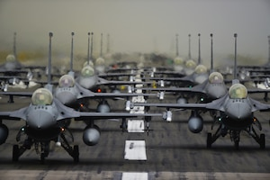F-16 Fighting Falcons line up in formation on the runway