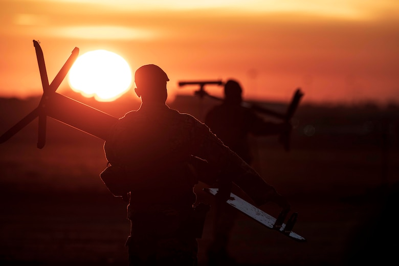 Flight instructors carry shooting targets to a training site