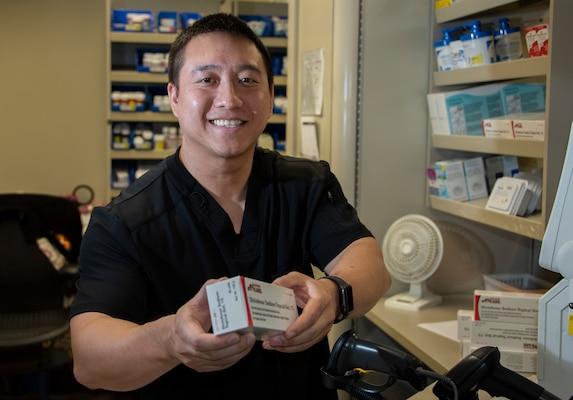 Huy Nguyen, pharmacist, dispenses a prescription in the main pharmacy at Brooke Army Medical Center, Joint Base San Antonio-Fort Sam Houston.