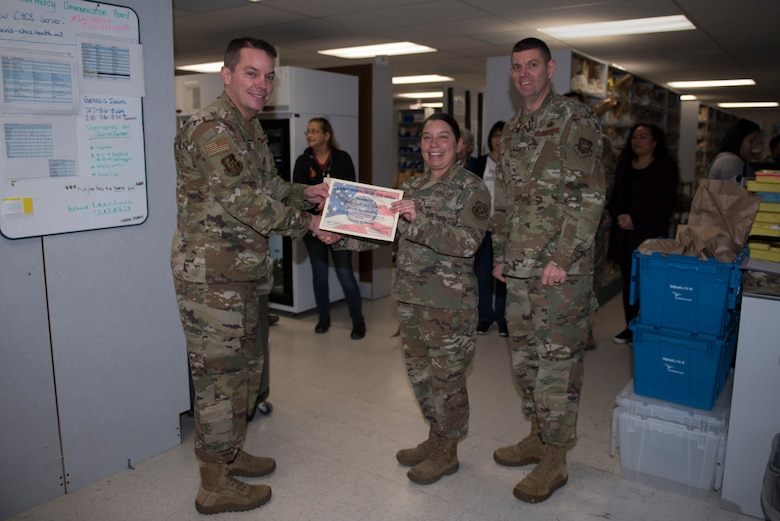 U.S. Air Force Col. Jeffrey Nelson, left, 60th Air Mobility Wing commander, and Chief Master Sgt. Derek Crowder, right, 60th AMW command chief, recognize Master Sgt. Andrea North, center, 60th Medical and Diagnostics Therapeutic Squadron satellite pharmacy section chief, as the Warrior of the Week Jan. 7, 2020, at Travis Air Force Base, California. North was recognized as the 60th Air Mobility Wing Warrior of the Week for her efforts in keeping the pharmacy running during a base power outage Nov. 27, 2019. The Warrior of the Week program recognizes Airmen who have made significant contributions to their unit. (U.S. Air Force photo by Airman 1st Class Cameron Otte)